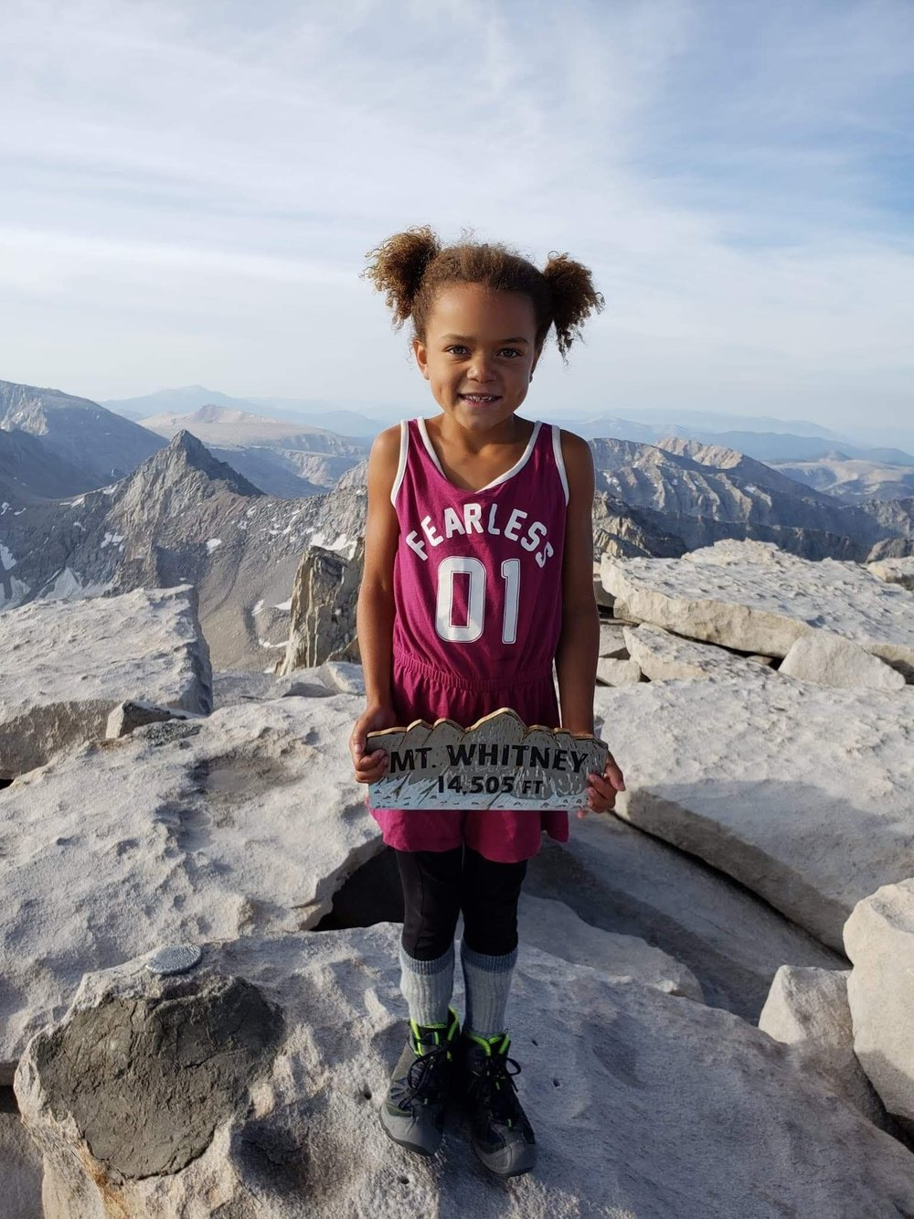 My 6 year old on top of Mt. Whitney - My daughter is 6 years old and she just made it to the summit of Mt. Whitney in the USA a few days ago (July 2018). Please note that the actual name of this mountain is Tumanguya, named by the Pi Ute indigenous people  before that region of the Sierra Nevadas was colonized.My daughter's name is Eva Luna.  I believe she may be the youngest girl to have done this on record in the last ten years. Research shows that a six year old boy did it in October 2016. So far, the number of children to have done it at the age of 6 and under are 3 kids (at least on record). Eva Luna wanted to be one of the youngest girls on record and it seems like she is probably as well as the youngest African American person on record. You can go here to learn more about why this is significant within a sport in which we rarely see more African Americans doing 14k+ mountains-- or mountaineering and extreme hiking in general. The Mountaineers also addresses this here.Tumanguya is the tallest mountain in the contiguous USA at 14,505 feet. 22 miles, but the high elevation and thin air can make it grueling and feel like twice as long for many who have attempted the ascent. She persevered through mild symptoms of altitude sickness. She woke up at midnight to start the ascent with headlamp and with her daddy and nine year old brother. It took them nine hours, half in the dark. One of the photos below is of Eva Luna on my back while we hiked Yosemite when she was a baby. Learning about hiking all the time from our many adventures from Utah to Yosemite, and other places with great long trails. She thought it was normal that I had a 25lb baby on my back while hiking up mountains and other places for miles. My favorite was her on my back for ten hours while we hiked Bryce Canon in Utah.In one of the photos below, I was pregnant with Kiki (her younger sister) while Eva Luna was on my back (Yosemite).Eva Luna has seen me hiking while pregnant and has seen me hiking while having Kiki (younger sister) on my back. Same with me being pregnant with Miro (who was born in 2016). We have 4 kids now and they have all spent hours on my back, while our family hiked and camped. Also, her daddy is a mountaineer. It is part of our family culture. He was an amazing mentor and lead as he took Sun and Eva Luna to Tumanguya (renamed Mt. Whitney) and handled business.I can't emphasize enough, how much here older brother Sun, delivered as