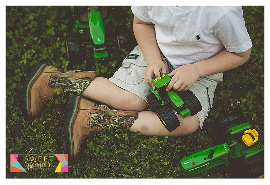 Young boy playing with his John Deere tractors