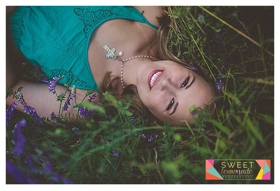 Senior girl photographed in green dress and purple flowers