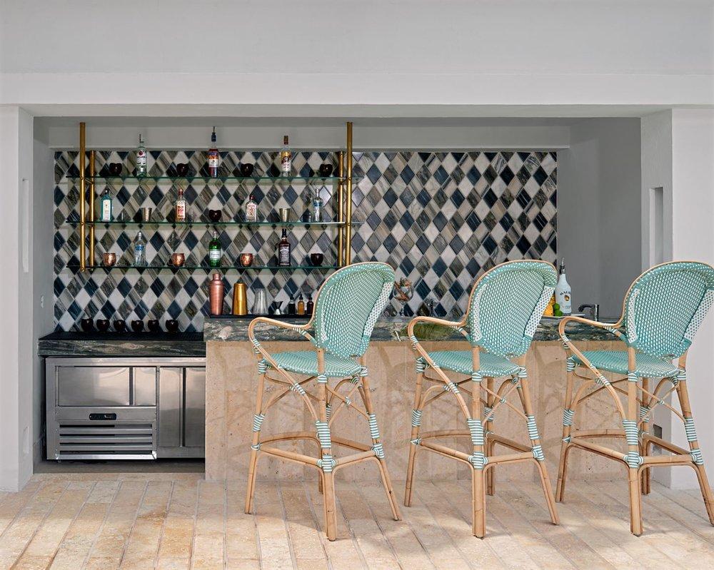 El área del bar junto a la piscina cuenta con una pared de mosaico con tres tipos de mármol, un mesón de mármol verde y banquetas de bar azul turquesa. Foto de  Tawfick Espriella .