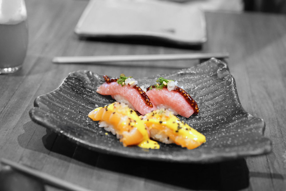 Toro , or belly tuna and salmon with an emulsion of traditional Peruvian yellow chili pepper sauce, sprinkled with sesame seeds.