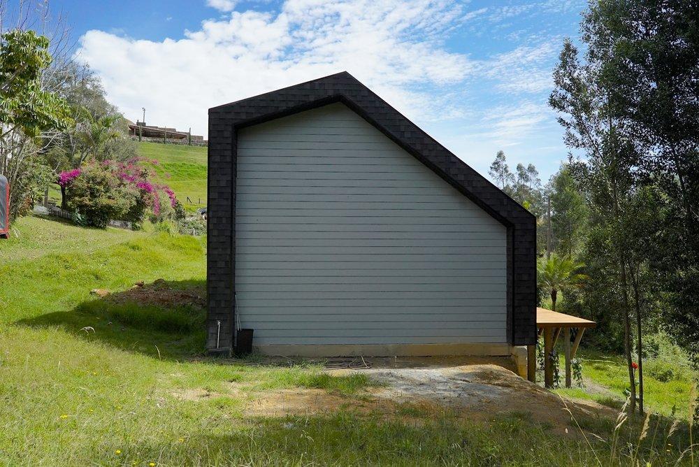 Mientras que la fachada frontal y posterior son cerradas para conservar la privacidad frente a sus vecinos, las laterales cuentan con ventanas amplias que inundan la casa de luz y vistas al bosque.