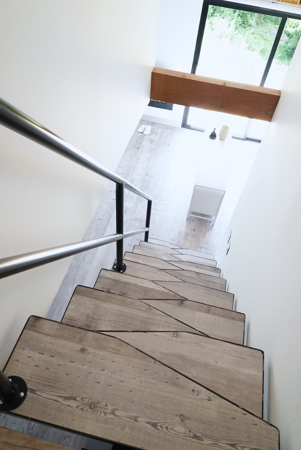 The unusual stairway design features alternating salient beams that facilitate the climb in spaces that are small and steep.