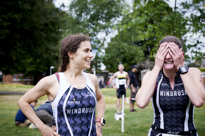 Two Windrush athletes in club kit looking happy and relieved after just finishing the race