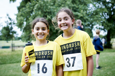 Two smiling girls in the park wearing yellow windrush aquathlon tshirts