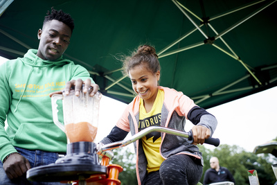 Girl wearing yellow tshirt on stationary bike with man wearing green hoodie standing next to her