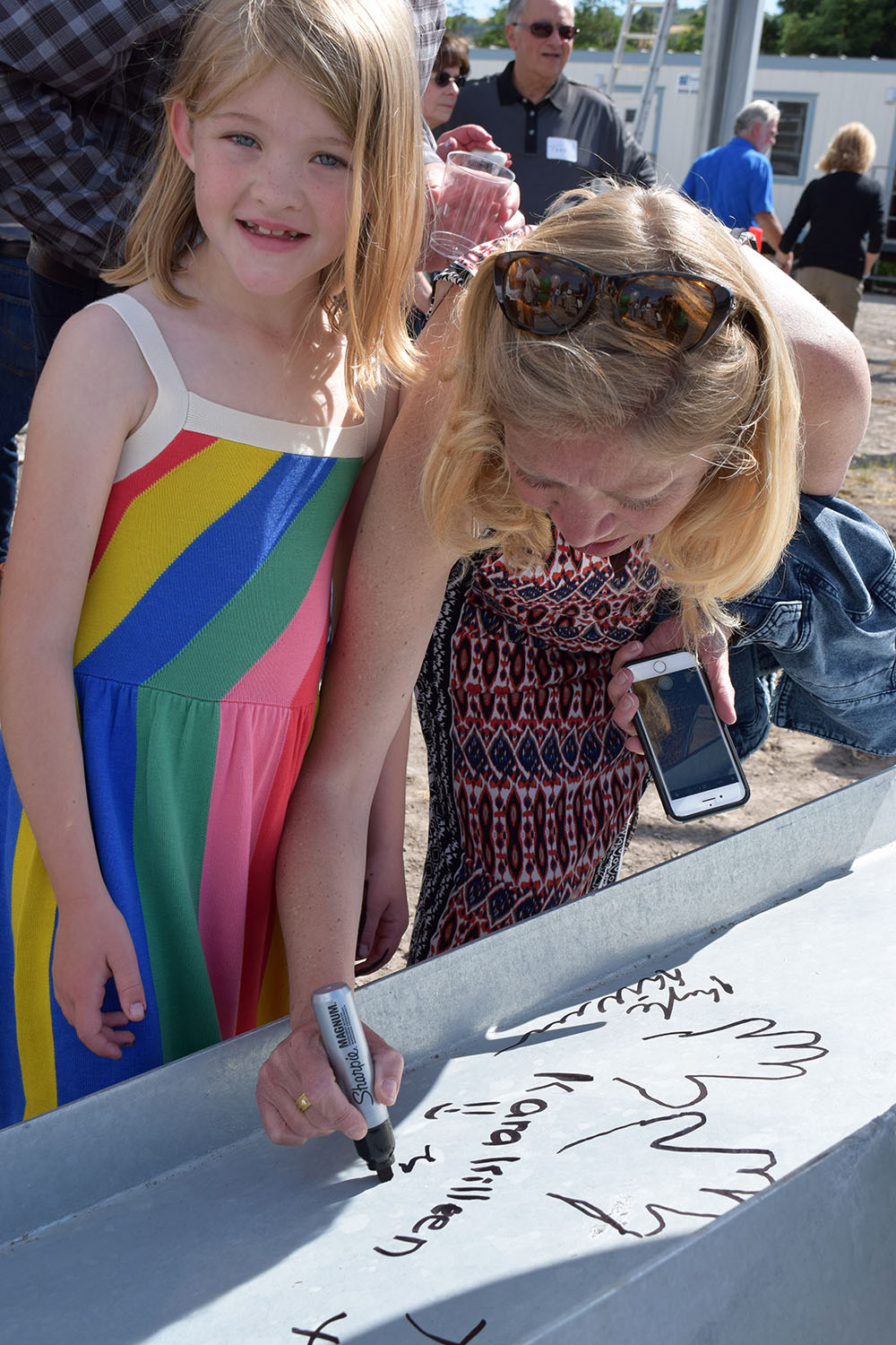 Sara Roche and her daughter Kara signing the beam