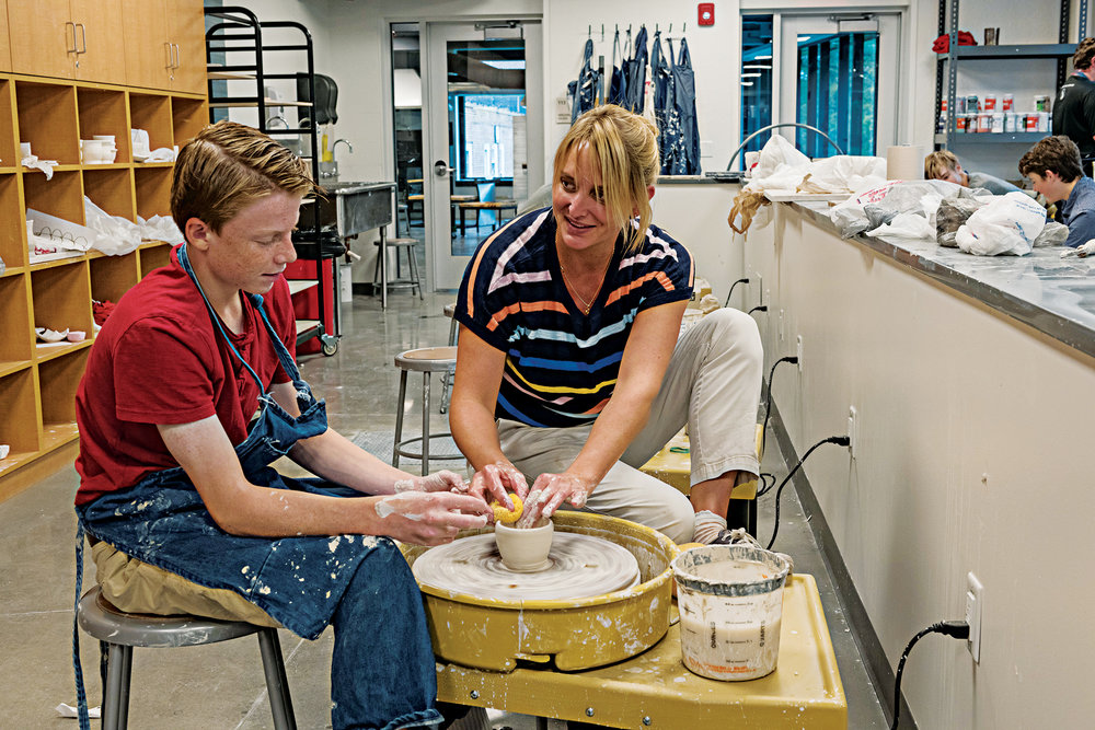 Soderberg works with a student at a pottery wheel