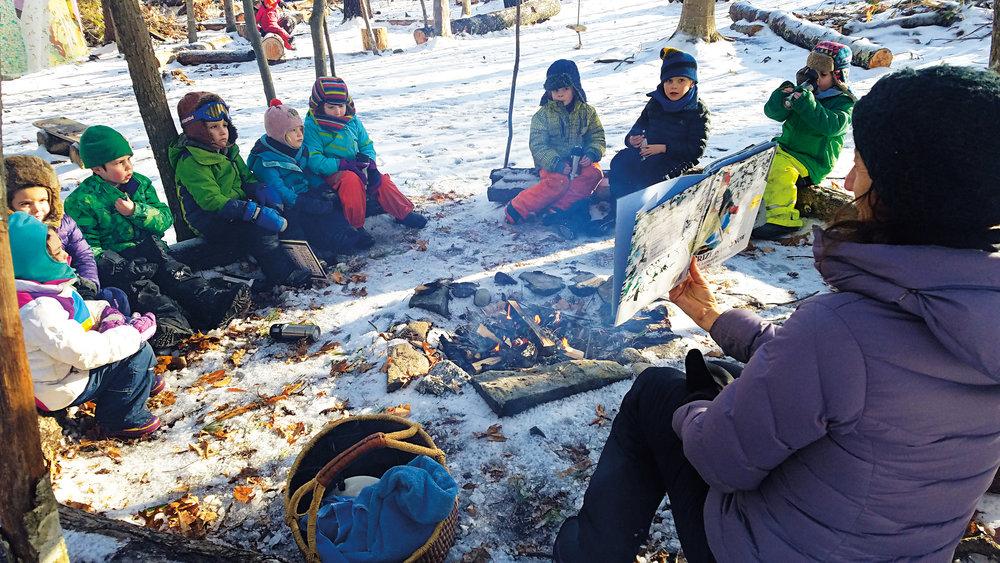 Anne Stires '94 reads to nature preschool and kindergarten students in the Salamander Woods outdoor classroom.