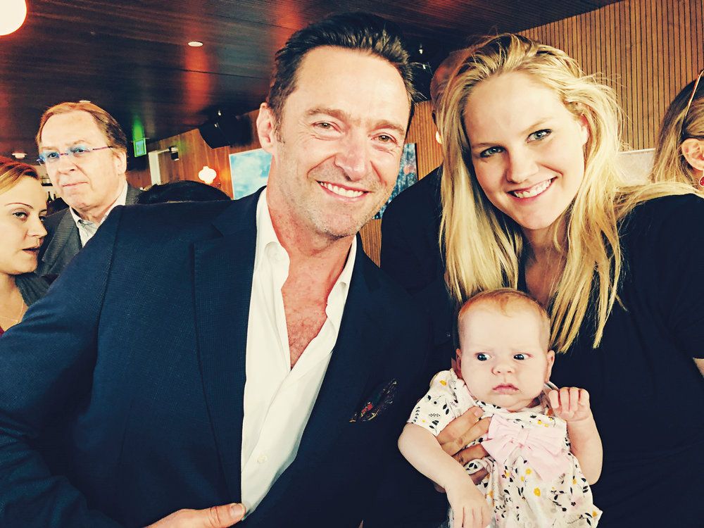 Audrey, grandaughter of Ted Baehr '64, posing with her mother, Evy, and her fan, Hugh Jackman.