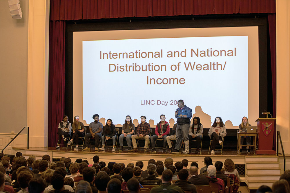 Above  Keith Dean '19 explains to students wealth distribution as it relates to the School population. T op right   Dean asks students to take a seat under the economic bracket that best represents them.