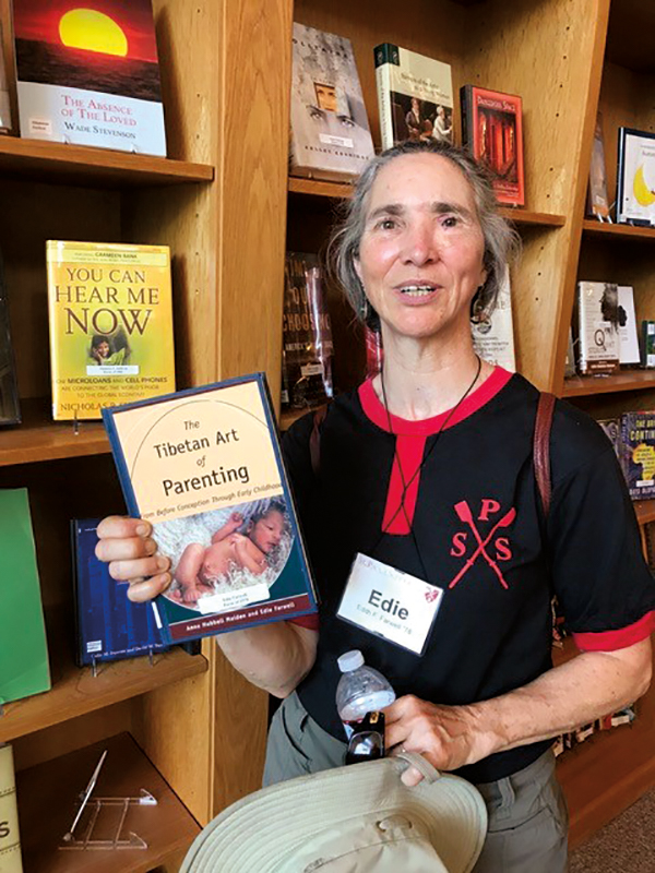 Edie Farwell '78 holding her book, The Tibetan Art of Parenting, in Ohrstrom Library.