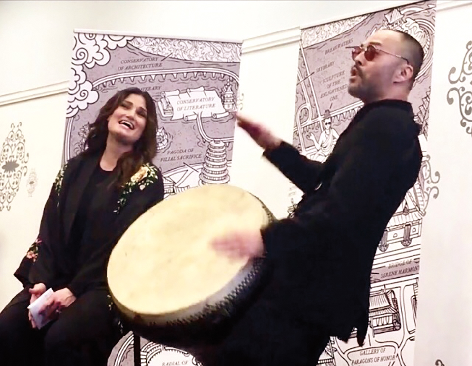 Lien performing at his book launch with Idina Menzel with a map inspired by the SPS grounds in the background.