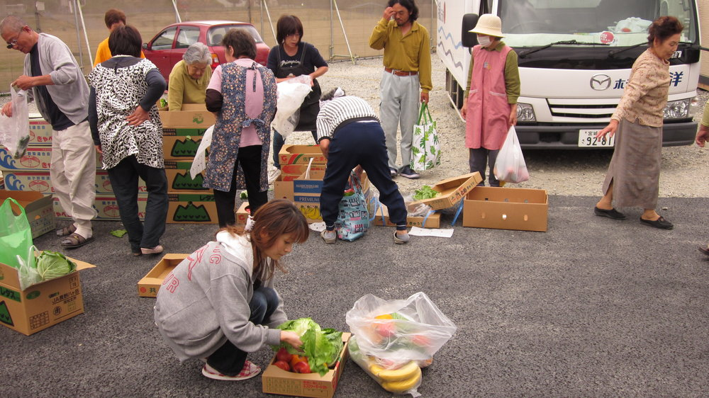 Temporary housing residents collect fresh vegetables delivered by O.G.A. for Aid