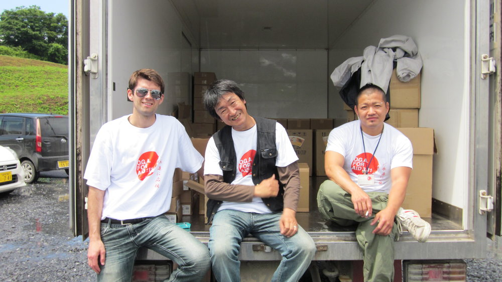 With O.G.A. for Aid's Kei Watanabe and a Hotel Kanyou associate, Choki Abe, delivering goods to a temporary living facility.
