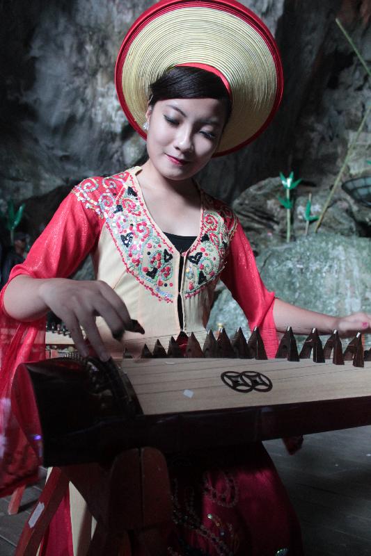 A woman plays the Đàn tranh ,  the Vietnamese zither, in Da Gao Cave, Halong Bay.