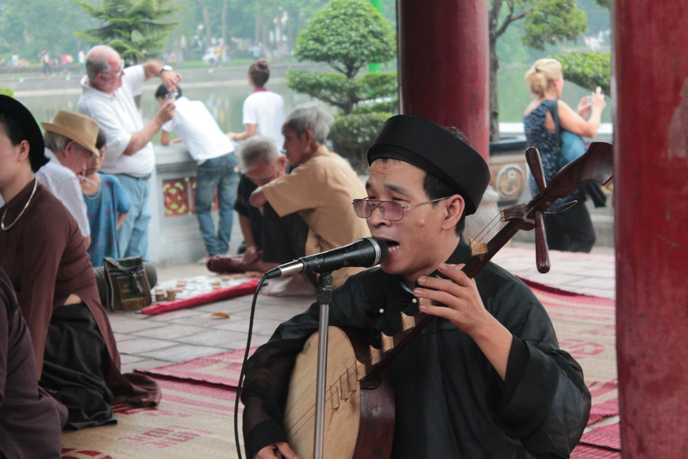 Musicians and tourists mingle at Đền Ngọc Sơn ,  or the Temple of the Jade Mountain, on the northern end of Hoàn Kiếm Lake in Hanoi.