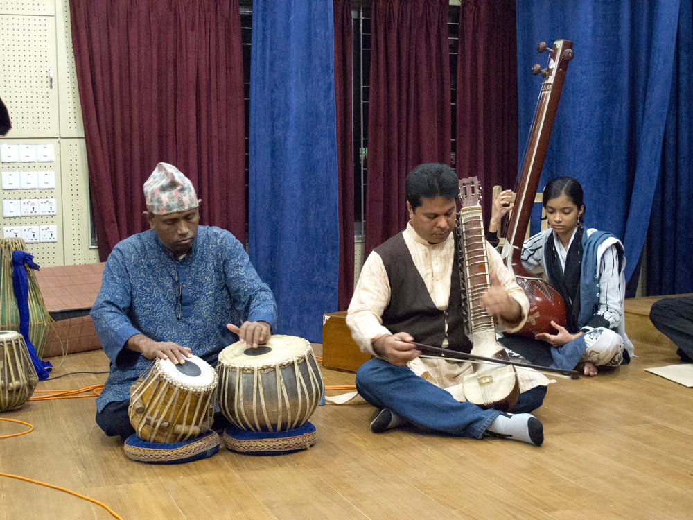 Musicians perform the tabla (hand drums), esraj (a bowed string instrument), and the tanpura (a fretless drone instrument). Photo by Shinobu Suzuki.