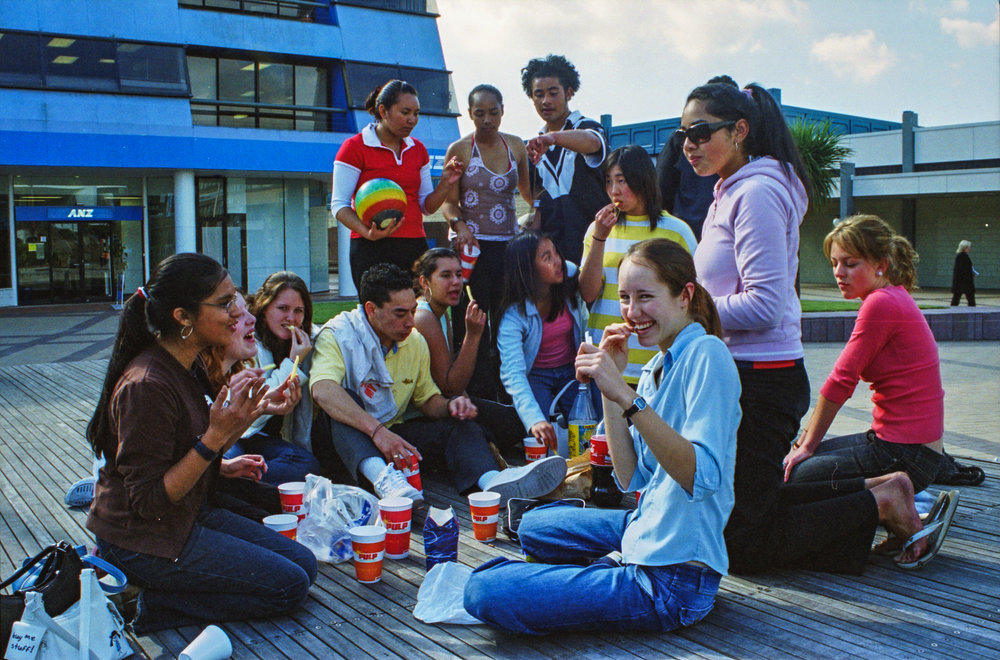 A group of young pepple eating hot chips outside of the Manukau City Mall.  Image Credit: Stjohn Milgrew. 2005.