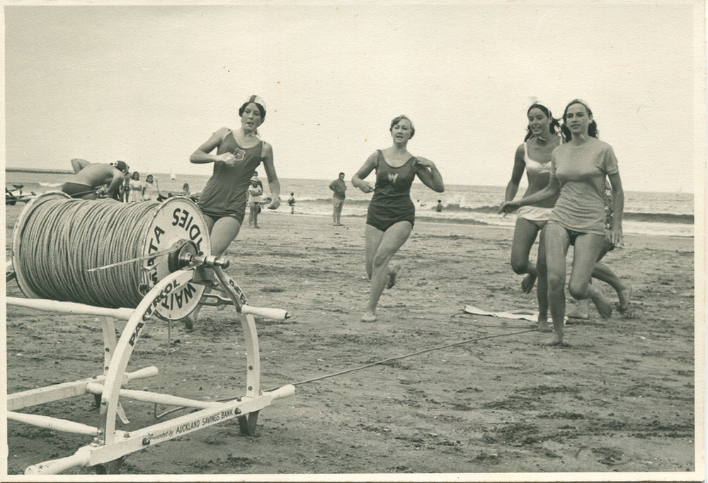 The Waitemata Ladies Surf Lifesaving Team running to get the reel at start of competition. Photo first printed in the Auckland Star 1969. Image Credit: Helen Gillespie.
