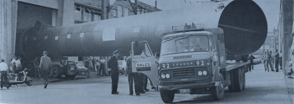 Large fabricating jobs consistently left the Auckland Waterfront shops bound for all parts of Auckland. This 15-ton chimney, 110 ft long, squeezes out the door in the 1960s to start a 14-hour journey to Kinleith onboard two transporters. Image courtesy of Kevin Shulz, Mason Bros Ltd.