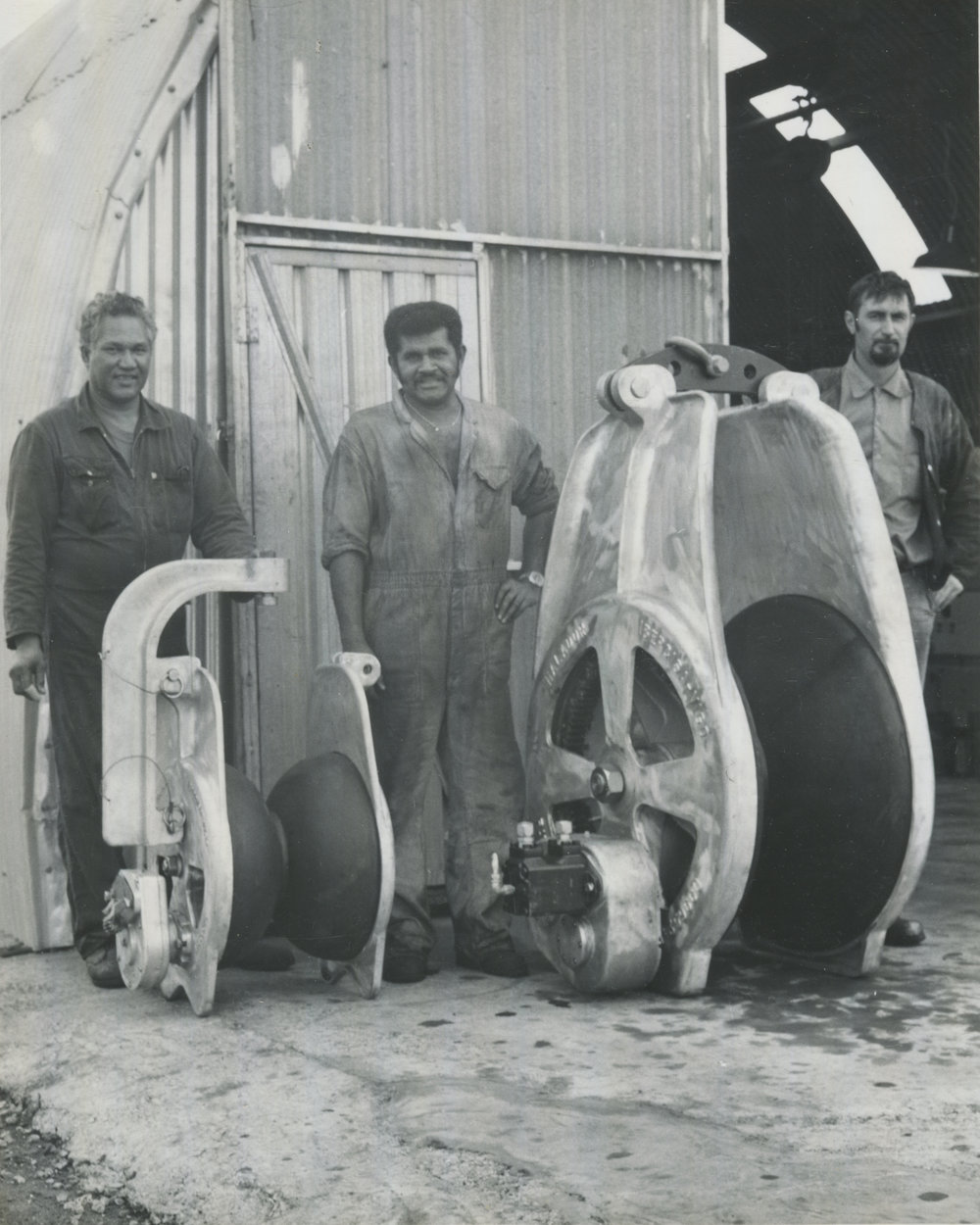 "The dock workers (Jack O'Brian, unknown and ""John the Pom"") standing with their ship pulleys in 1970s. Courtesy of Titan Engineering."