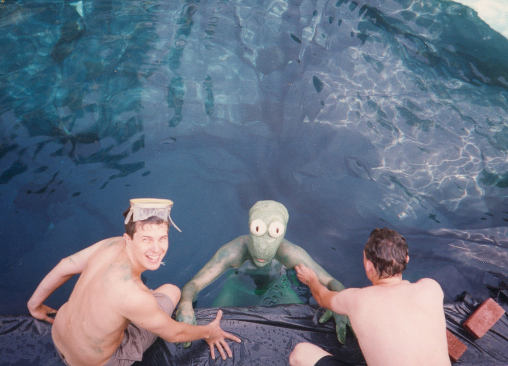 Two-time Emmy Award winning writer Kent Osborne (left) and SFX wizard/latex mask fabricator Jim Long (right) help to pull a lumpy green being (a.k.a. Mark)from the depths of a Reseda, CA swimming pool, circa 1993.
