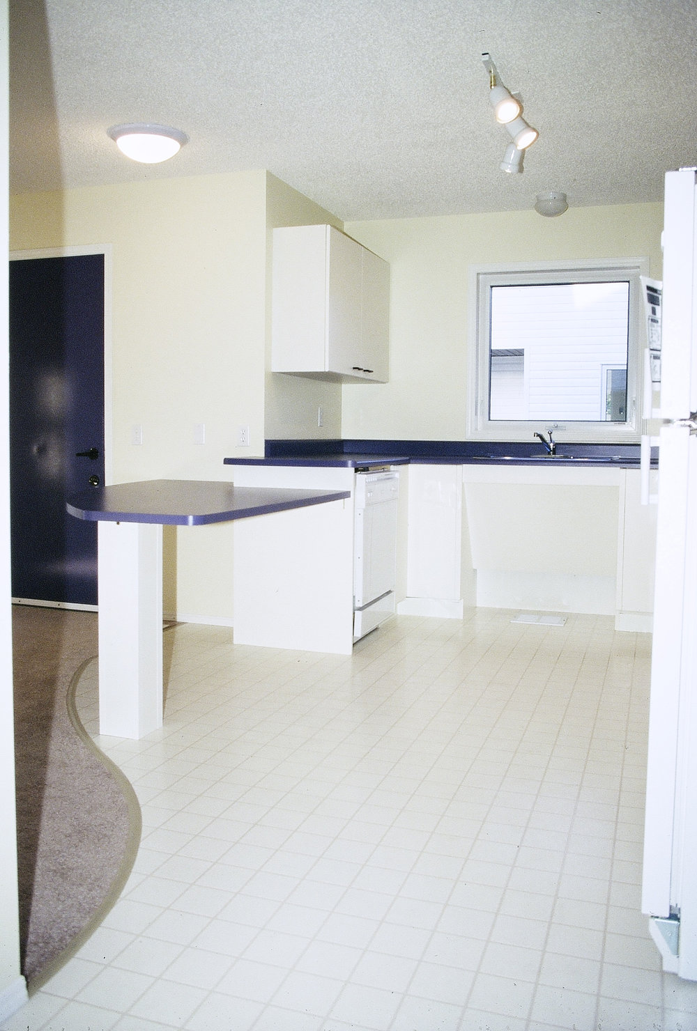 "The image above shows the kitchen area of the ground level accessible dwelling. Most of the counter height is the standard 3'-0"" from the floor. A lower counter, which is open underneath extends into the living space. The counter can serve as a workspace and eating area for someone sitting in a wheelchair. The sink is open underneath for easy wheelchair access."