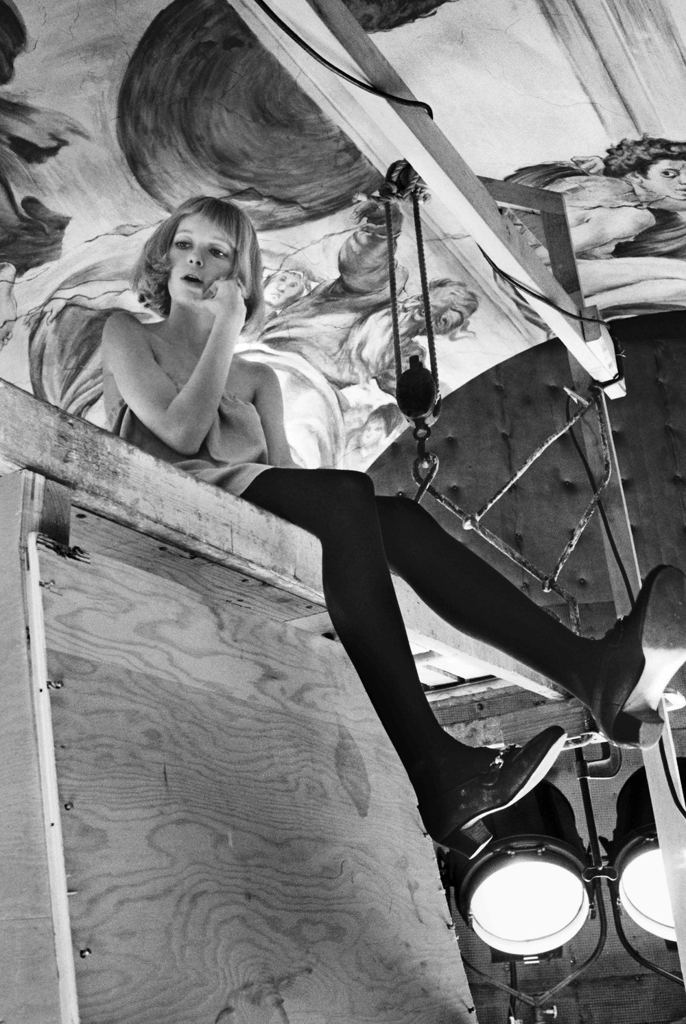 Mia Farrow perched long legged on the scaffolding of Rosemary's Baby during filming at Paramount Studios, 1967