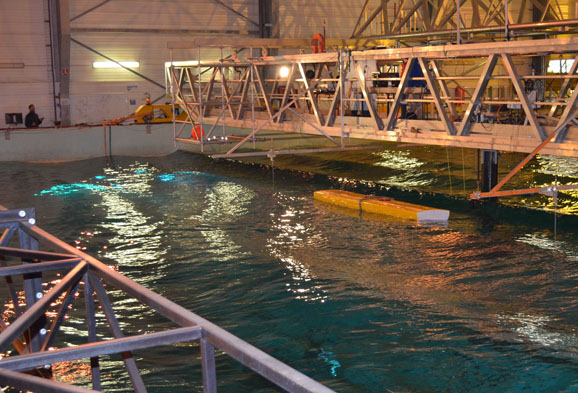 - A test series has been conducted at the ECN in Nantes as part of the EU-Project MARINET. This wave tank, one of the biggest worldwide, enables tests with the 1:5 scaled NEMOS-device. Due to the precise adjustments and reproducibility of the wave conditions, extensive hydro-mechanical parameter studies were carried out. The results of more than 200 tests will be integrated in the automation of the system during the upcoming field tests and the full-scale device.