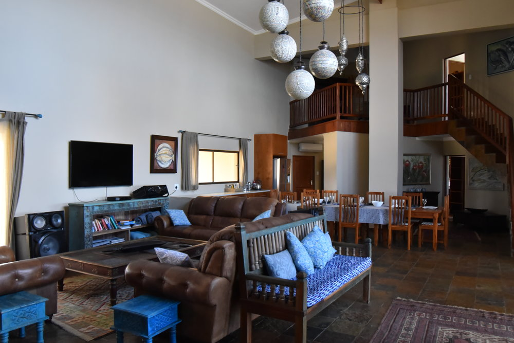 Living Area - The lovely living space is inviting, sit back and enjoy the coolness of your aircon while catching up on D.s.t.v. The bookshelf corner has lots to offer kids & adults. The comfy leather couches compliments all the other elements of the Villa.