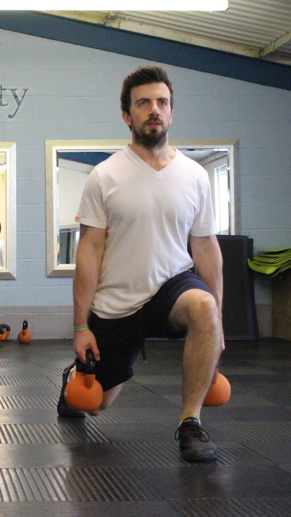 Dan, a personal trainer in Frome, exercises with kettlebells in the studio.