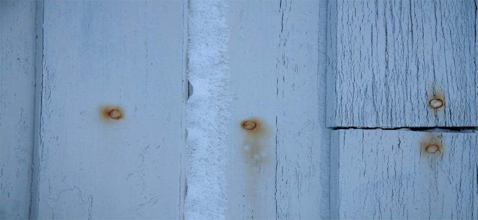 White fence, blue light, rusty nails