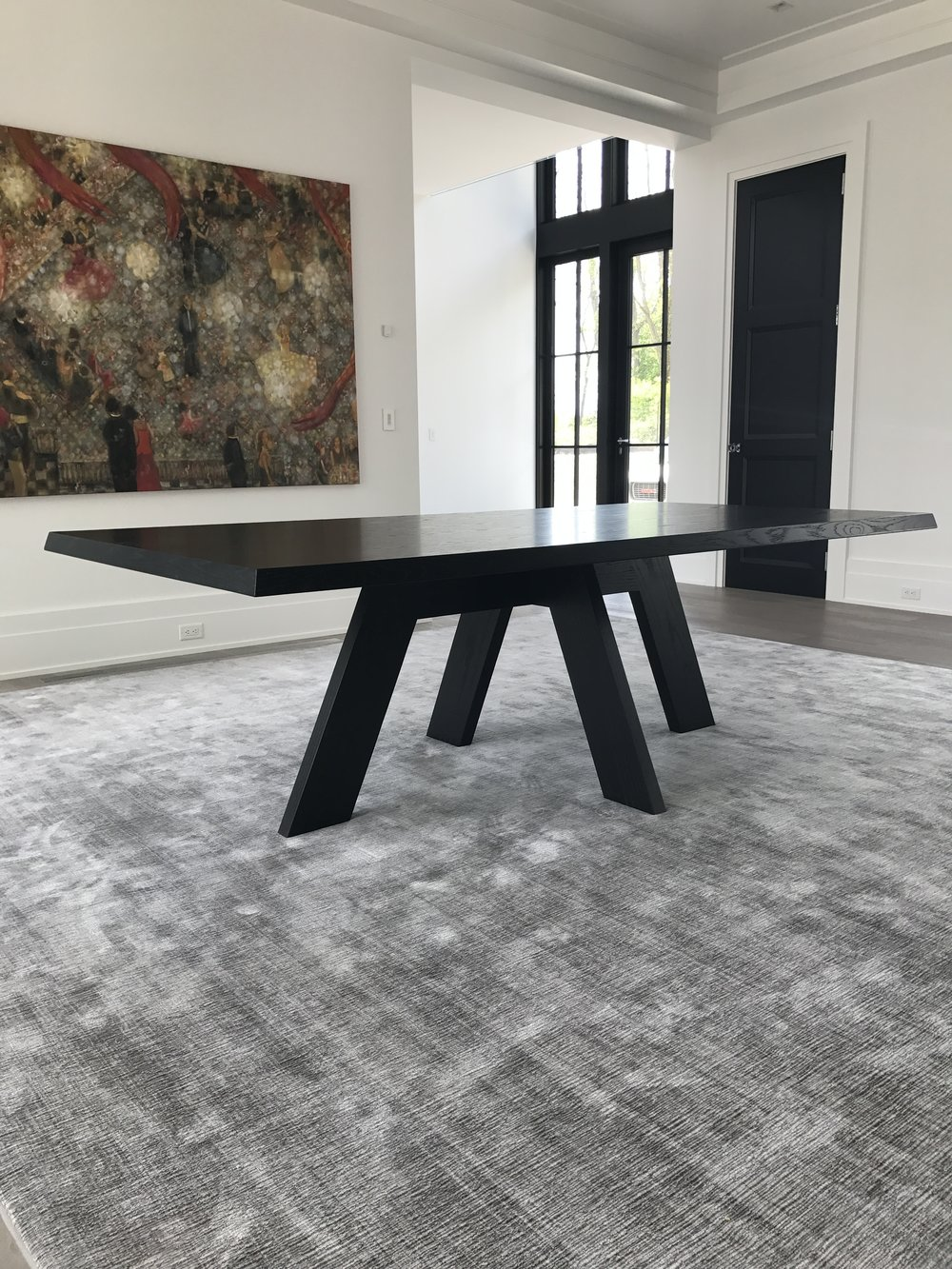 A rectilinear, ebonized white oak dining table.