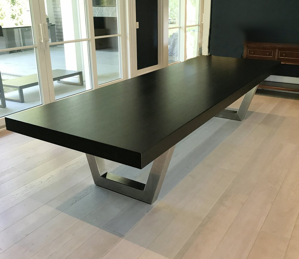 Ebonized white oak top with trapezoidal stainless steel legs.
