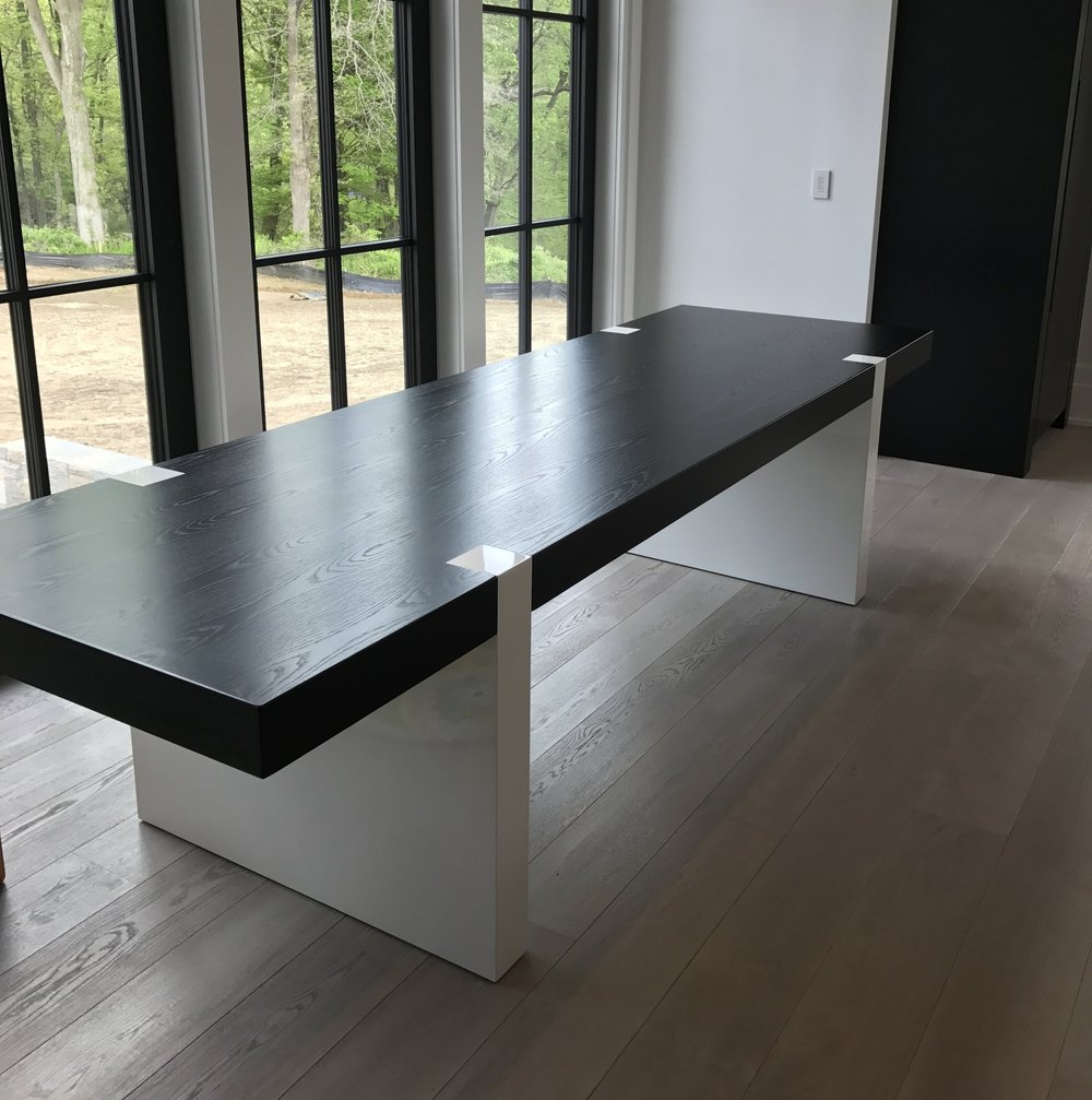 Ebonized white oak kitchen table with high gloss white legs.