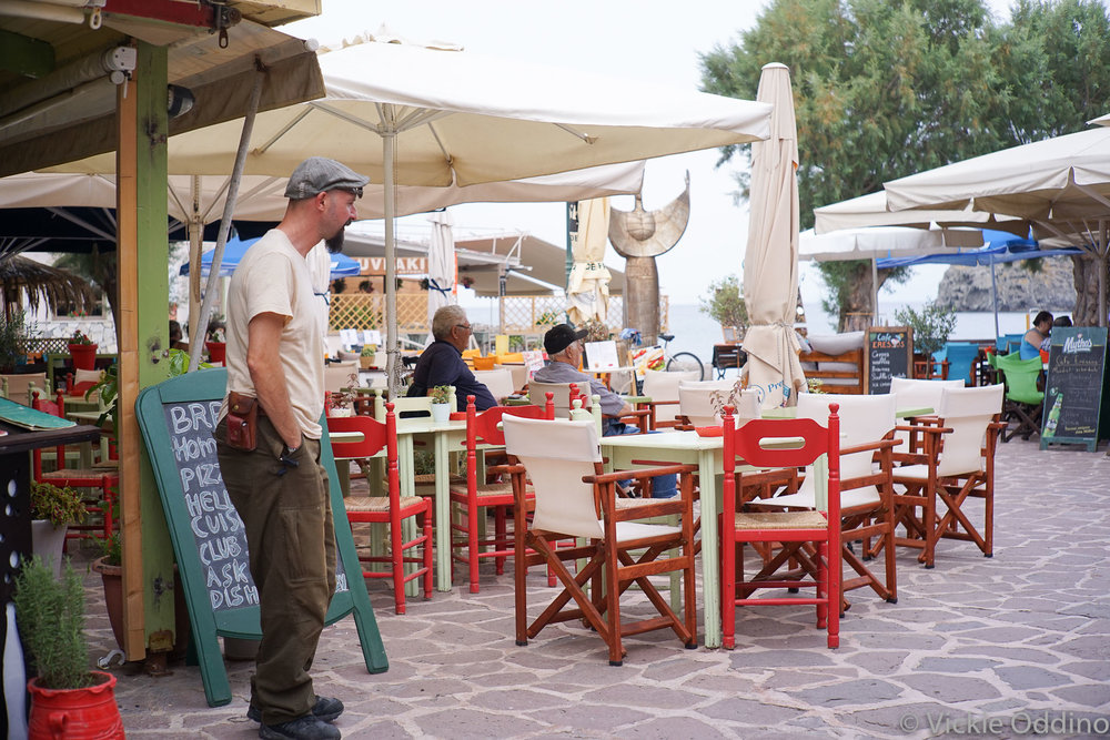 Erressos cafe next to the water, with a monument to Sappho in the middle background