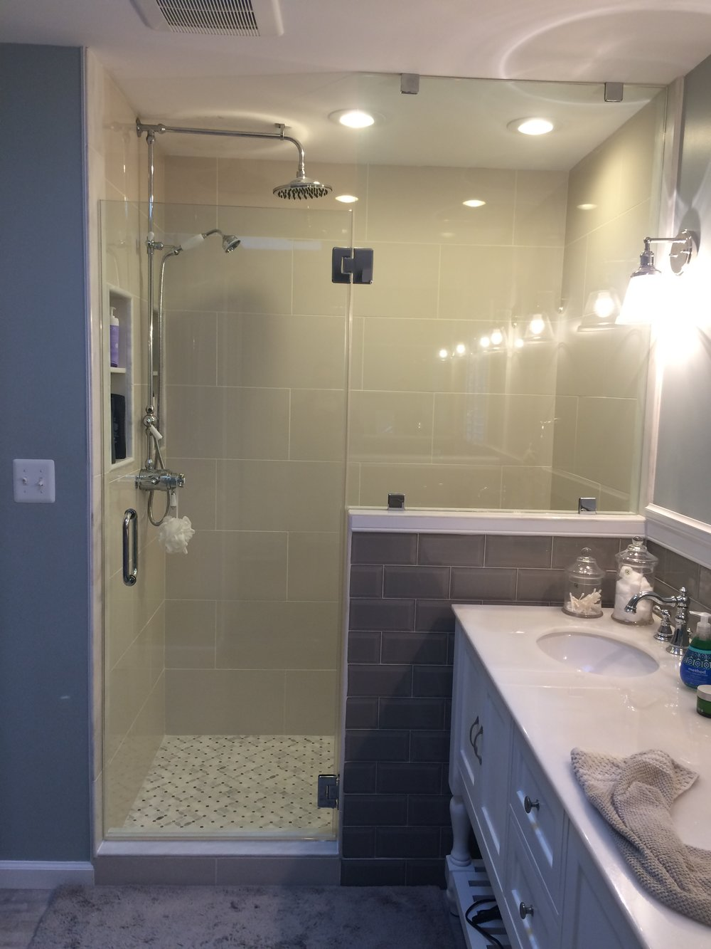 The new shower is enclosed by a custom frame-less glass shower door designed and installed by our friends at Woodbridge Glass Co.