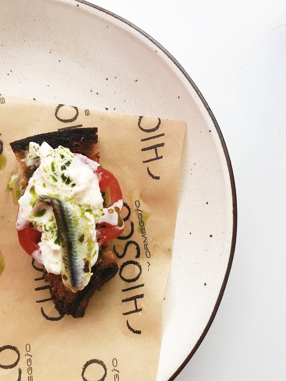 Bruscetta caprese: Sourdough, oxheart tomato, stracciatella, white anchovy.