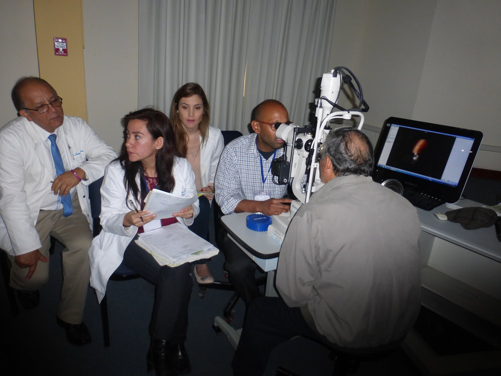 Dr. Manjool Shah examining a patient with projection onto a video screen to assist in teaching the observing doctors and residents