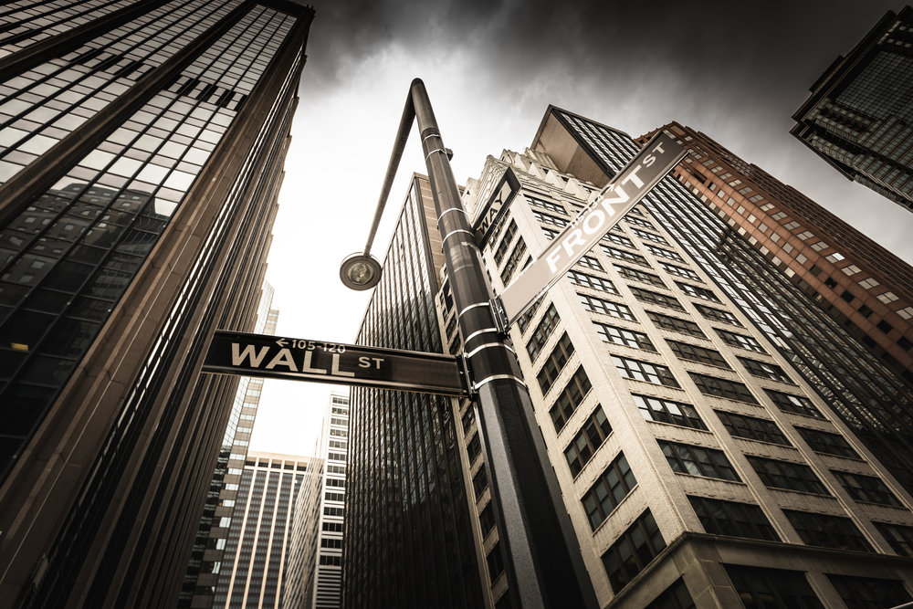Photo of Wall Street skyline with street sign.