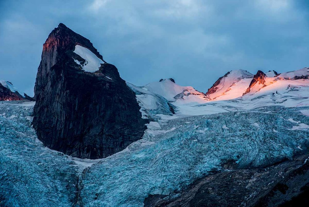 First light hitting the Pigeon Feathers. Houndstooth Peak is the prominent peak coming out of Bugaboo Glacier. Bugaboo Group in the Purcell Mountain Range. British Columbia, Canada.  © Neil Ever Osborne