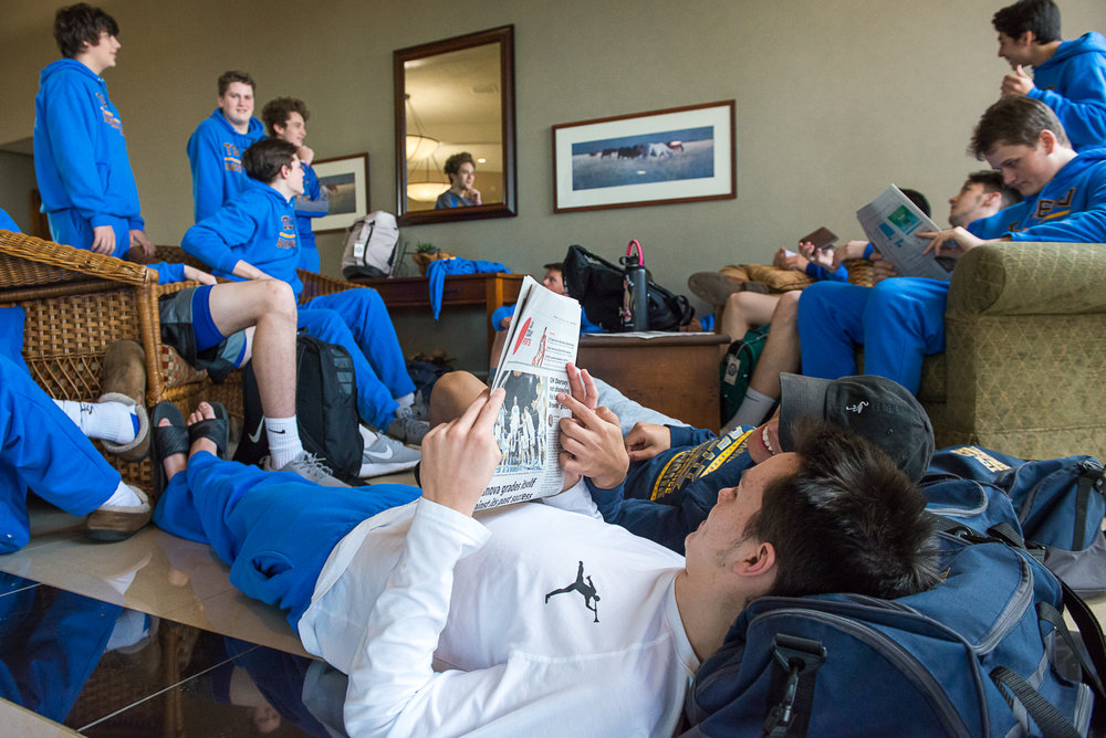 Conner Marchant and Santana Hutchinson read the sports section in the lobby of the team's hotel while the players relax at the beginning of the state 2A basketball tournament.