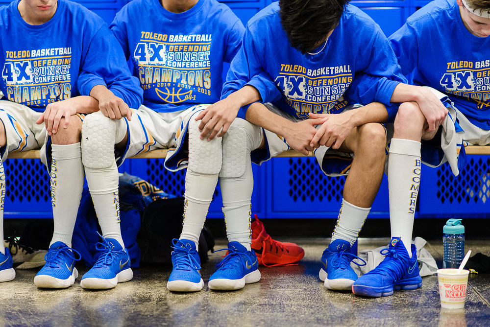 The 2A Toledo boy's basketball team bow their heads in the Boomers' locker room before their Saturday, Feb. 24 playoff game against Lost River at home. The Boomers have gone two years without an attendance at the state tournament in Pendleton, Ore., and hope to end that drought in 2018.