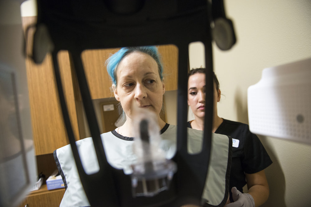 Timberly Eyssen, left, prepares for Dental Assistant Sam Mattix to take an X-ray of her teeth at Affordable Dentures in Vancouver on Friday morning, July 13, 2018. A skydiving accident in 2011 left Eyssen with a broken neck, which eventually lead to a severe opioid addiction. After years of drug abuse, Eyssen attempted suicide in in April of 2017, but has since begun a treatment with Suboxone, which helps to treat her pain and addiction.