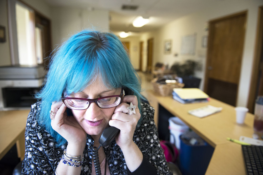 Timberly Eyssen plugs her ear to better hear a phone call while confirming patient appointments during her volunteer job at Battleground Health Care on Friday afternoon, July 6, 2018. Eyssen began volunteering at the clinic after she said they helped her with her addiction treatment, and decided she wanted to give back to the facility.