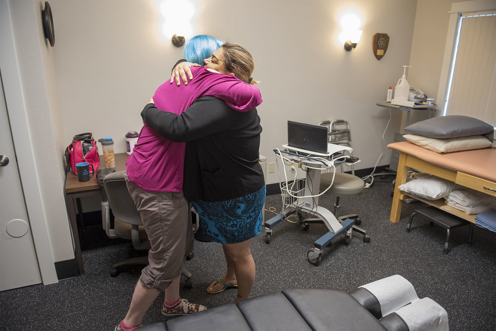 Timberly Eyssen hugs Chiropractic Physician Gloria Arroyo-Grubbs during a chiropractic visit at Battleground Health Care after Eyssen remarks that her neck has improved since their last vist, on Wednesday afternoon, Aug. 25, 2018.