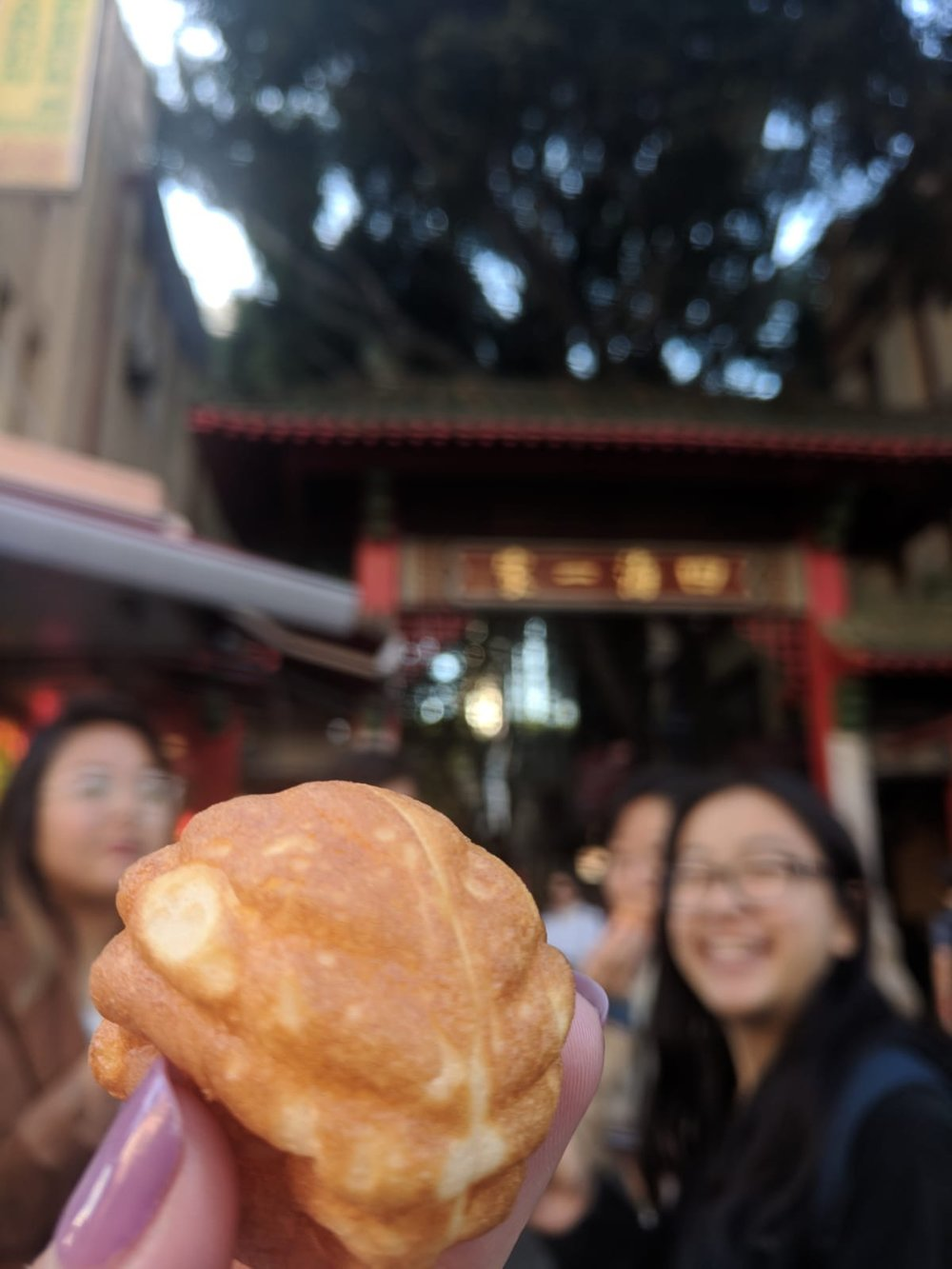 Ally & cohort friends eating Emperor's Cream Puffs in Chinatown.