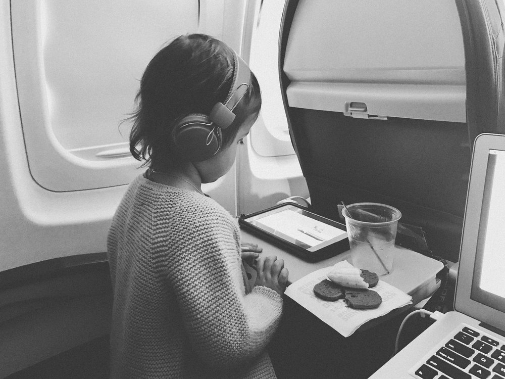 black and white image of a young girl on plane with her iPad and snacks