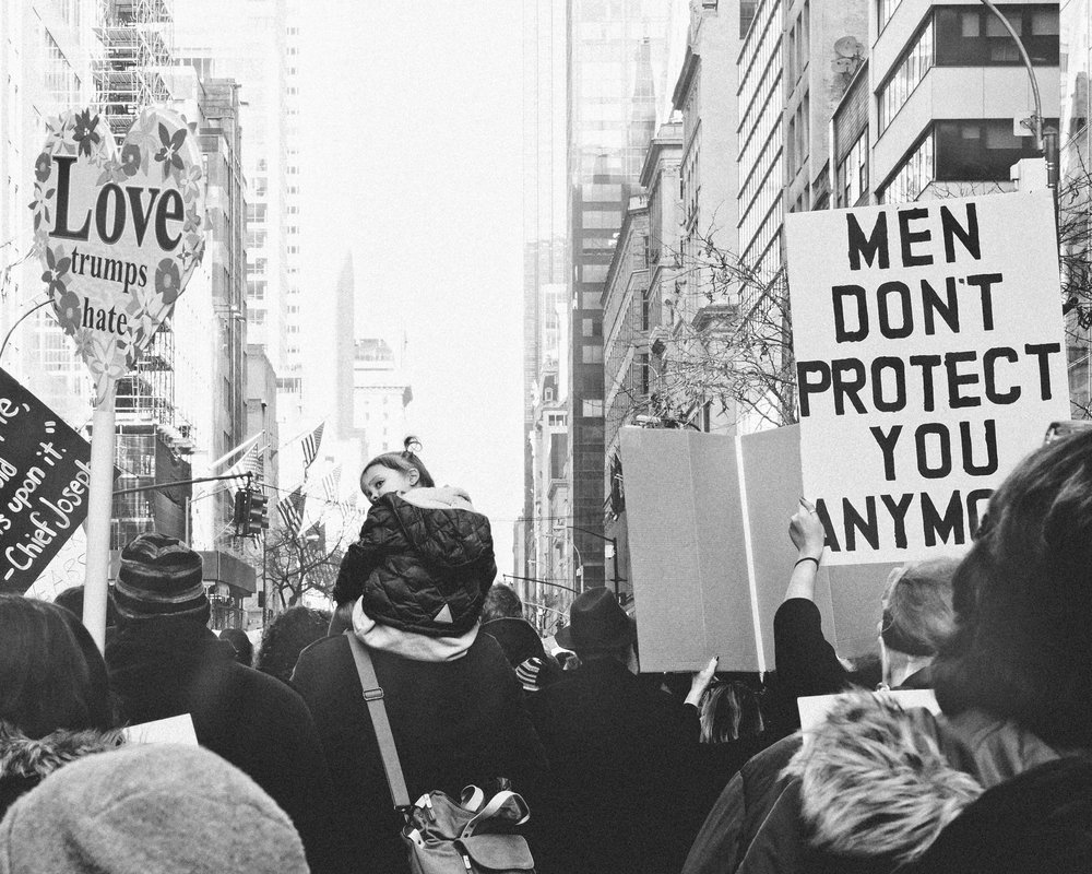 black and white image of a young girl on her father's shoulders at the women's march